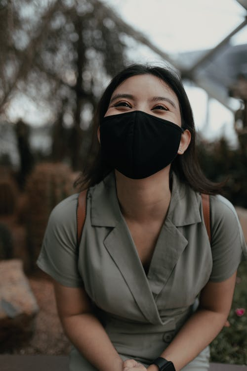 Cheerful Asian female in black protective mask and casual clothes standing on street and looking away in daytime