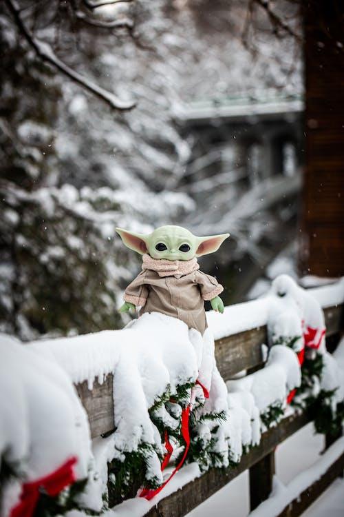 A Toy Yoda on a Wooden Railing