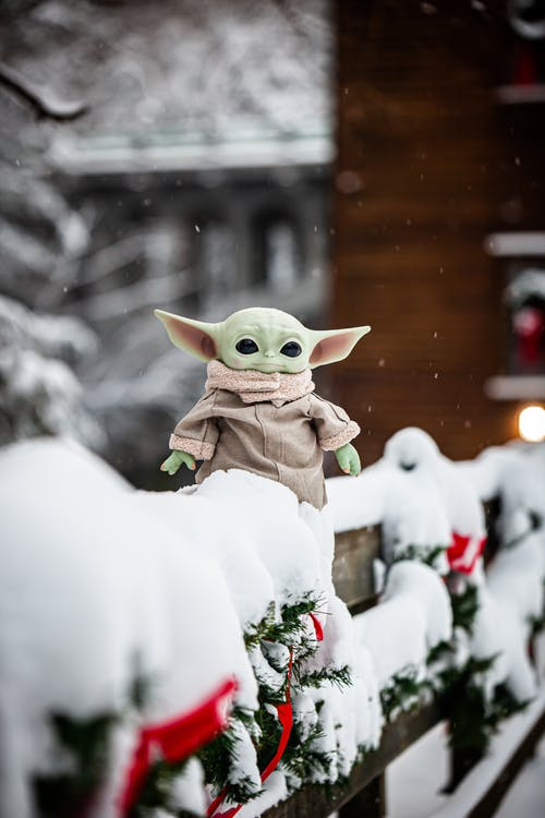 A Toy Yoda  Out in the Snow on Wooden Railings