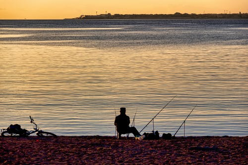 Silhouette Shot of a Person Fishing on the Lake