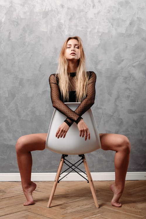 A Woman Legs Apart in Sitting on a Chair