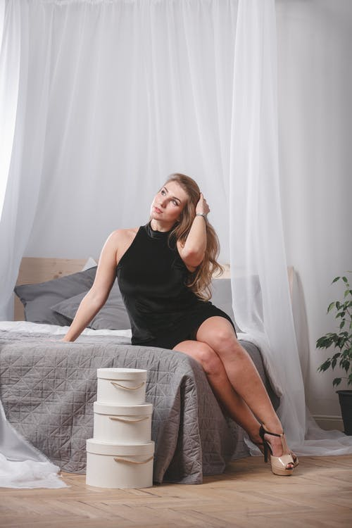 A Woman in Black Dress Sitting on a Bed