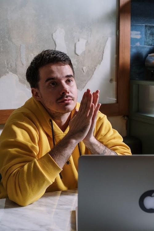 Người đàn ông Mặc áo Choàng Vàng Ngồi Trước Macbook Màu Bạc