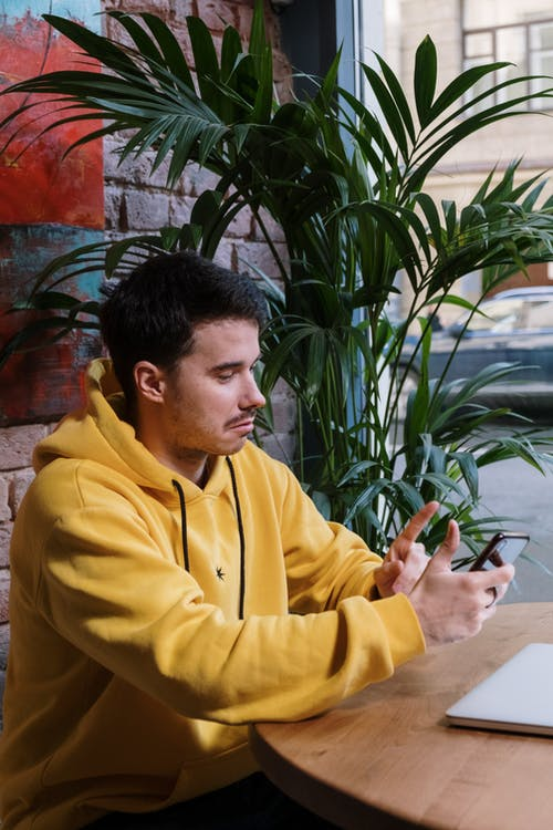 Man on a Yellow Jacket Holding a Cellphone