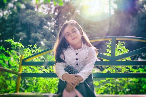 Girl Sitting on Bench Near Plants
