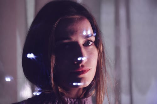 Peaceful young woman with light spots on face looking at camera