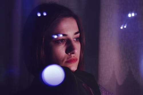 Through glass of young upset ethnic female with long brown hair looking away thoughtfully while resting in dark room near window reflecting light glares