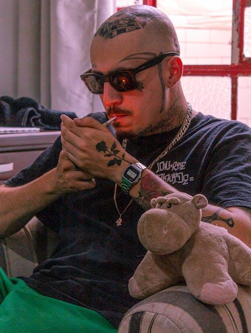 Brutal tattooed man lighting cigarette