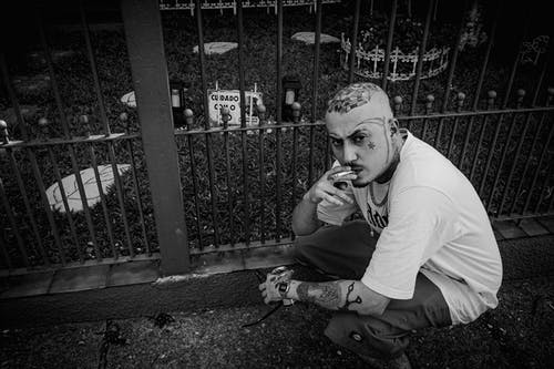 Black and white from above of serious tattooed male smoking cigarette while sitting on haunches near metal fence on street