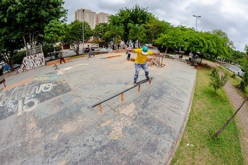Active faceless man skateboarding on rail