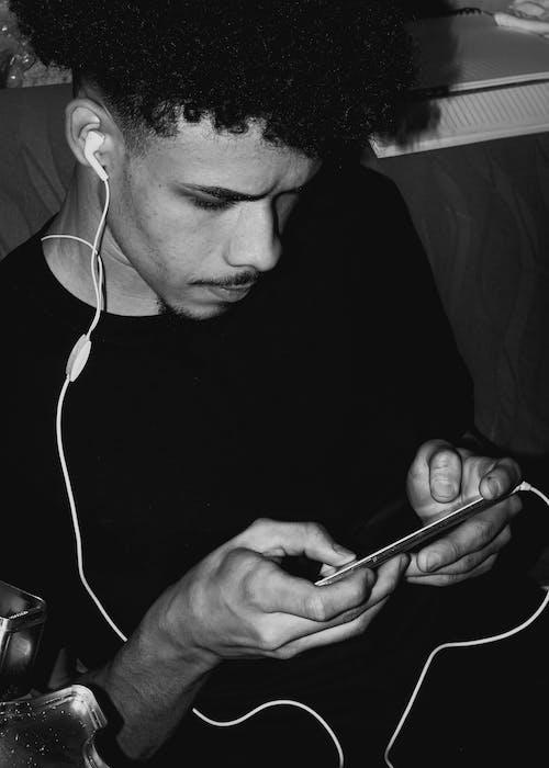 Pria Berkemeja Leher Kru Hitam Menggunakan Smartphone