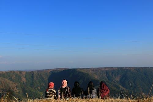 Backside of Women Sitting on Grass