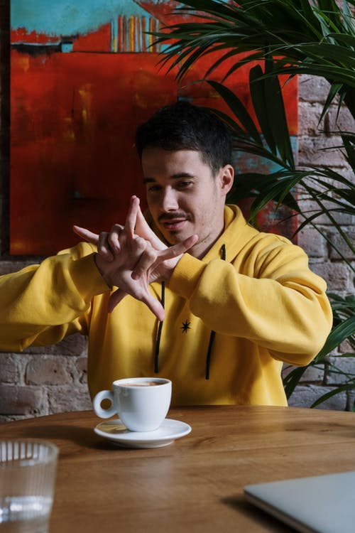 Người đàn ông Mặc áo Choàng Màu Vàng Cầm Cốc Sứ Trắng