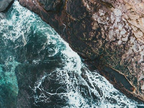 Foamy ocean with fast water flows against mount