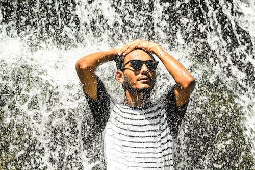 Mann, Der Weißes Hemd Und Sonnenbrille Steht, Die Auf Wasserfällen Stehen