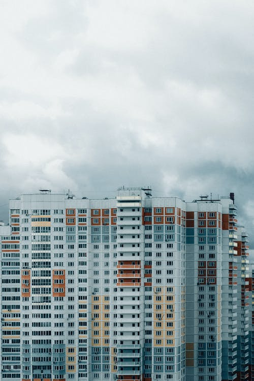 Exterior of high modern colorful residential building with balconies located in megapolis district on cloudy day in daytime