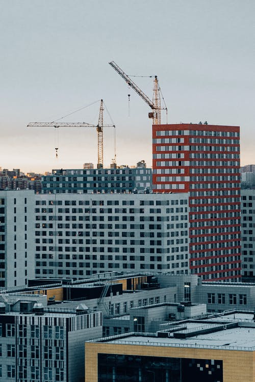 Cityscape with contemporary residential buildings and building crane on cloudy day
