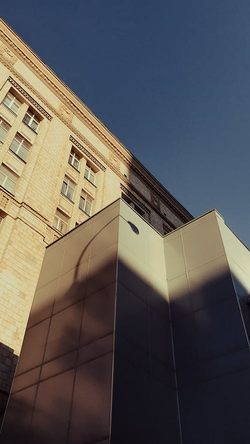 From below of corner of contemporary gray building with geometric pattern located near high residential brick house against cloudless sky in daytime