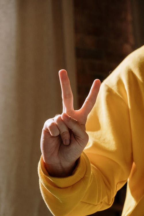 Person in Yellow Long Sleeve Shirt Showing Right Hand