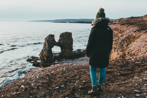 Back view of faceless female tourist in outerwear admiring wavy ocean and rocky formations from beach during trip
