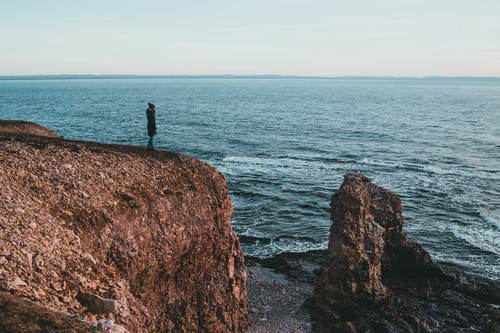 Side view of unrecognizable female traveler in warm outerwear and hat admiring wavy ocean while standing on rocky cliff under sunset sky