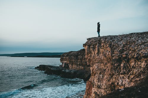 Unrecognizable woman standing on rocky cliff at seaside under cloudy sky