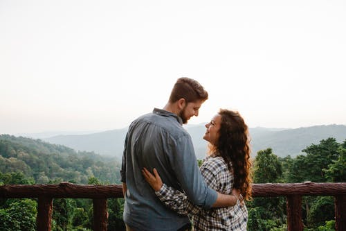 Back view of happy young romantic couple cuddling and looking at each other while standing on terrace against picturesque lush forest in mountains