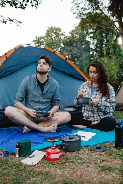 Full body of young male camper launching drone while sitting near tent with girlfriend having lunch during romantic trip in nature