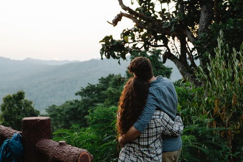 Anonymous romantic couple cuddling and enjoying mountain view in nature