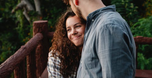 Side view of crop unrecognizable young guy embracing and kissing forehead of happy girlfriend while standing together on wooden terrace in forest
