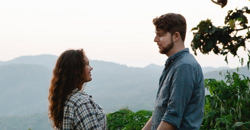 Side view of beloved young man and woman in casual clothes smiling and looking at each other during trip in green highlands