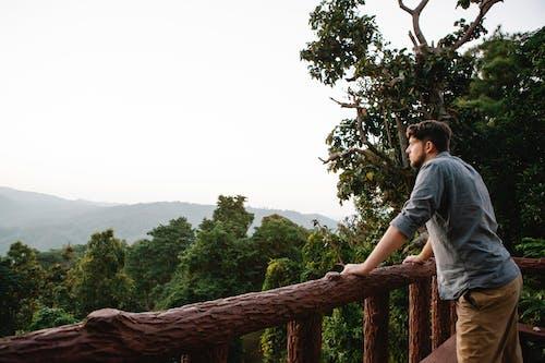 Pensive young guy enjoying mountain view from wooden terrace