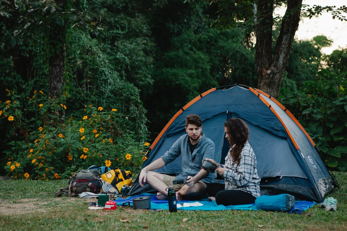 Young couple relaxing near tent during romantic trip in forest