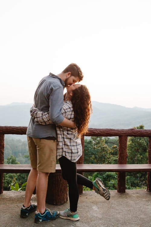 Side view of stylish young travelling couple in casual clothes hugging and kissing on observation deck in mountainous valley