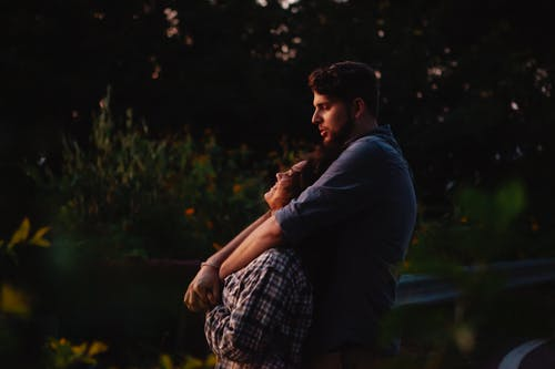 Loving young couple cuddling and enjoying sunset in nature