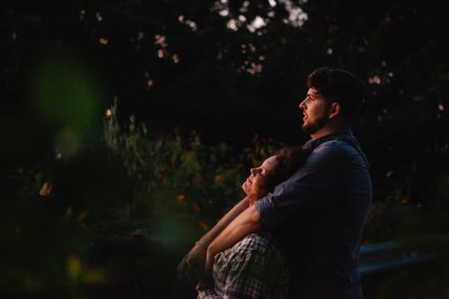 Dreamy young couple hugging while resting in nature at sunset