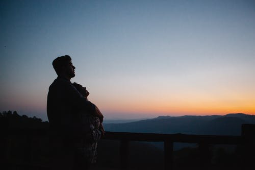 Silhouette of happy couple against picturesque mountains in sunset