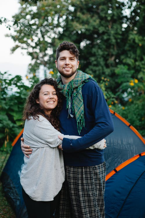 Young glad couple smiling near tent among green trees