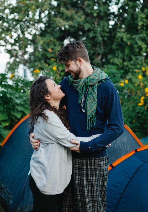 Cheerful young couple looking at each other and smiling near tent among trees with verdant foliage