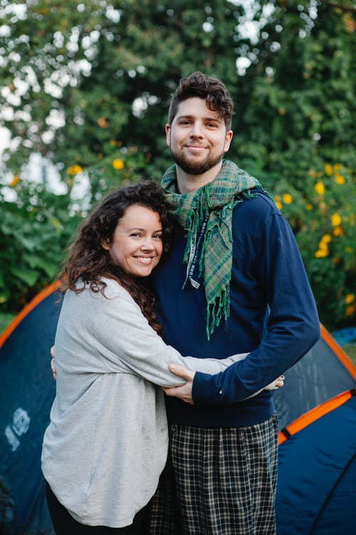 Smiling delighted couple hugging near blue tent in forest