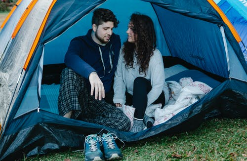 Loving happy couple resting in tent on green grass