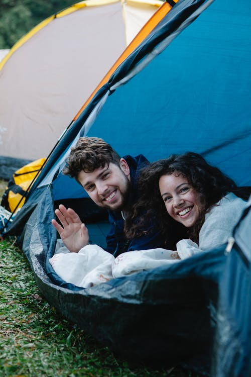 Young cheerful couple smiling and looking at camera while resting in tent on green grass