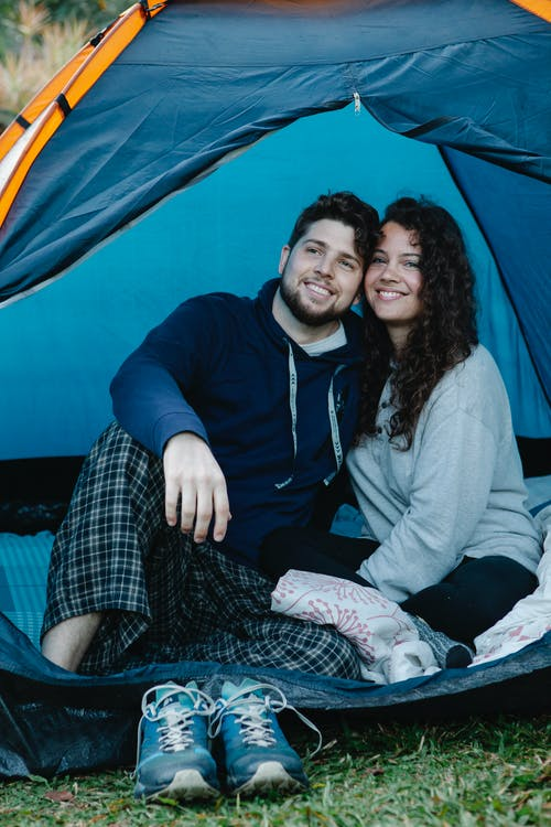 Positive young couple in casual outfit smiling and resting in tent on fresh green grass in nature