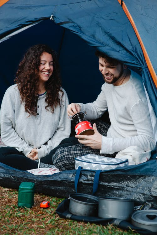 Cheerful young couple in pyjamas sitting in camping tent and having breakfast while spending holidays together in nature