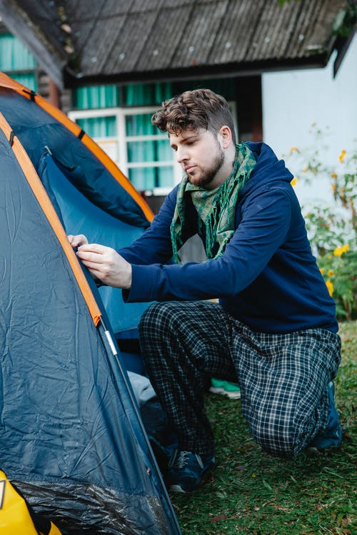 Young man in casual wear setting up camping tent beside farm house while spending holidays in nature