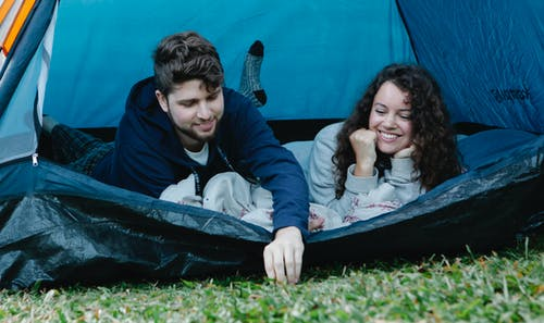 Young cheerful couple lying in camping tent while enjoying summer holidays together in countryside