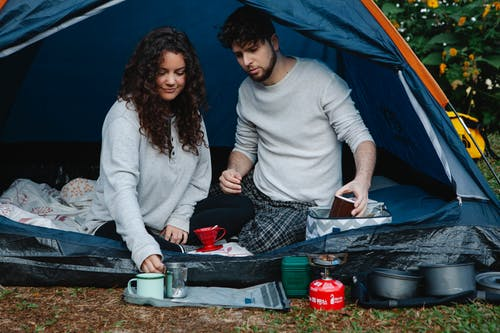 Young couple having breakfast sitting in tent
