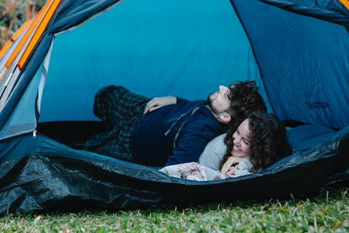 Young happy couple lying together in camping tent and enjoying weekend in countryside