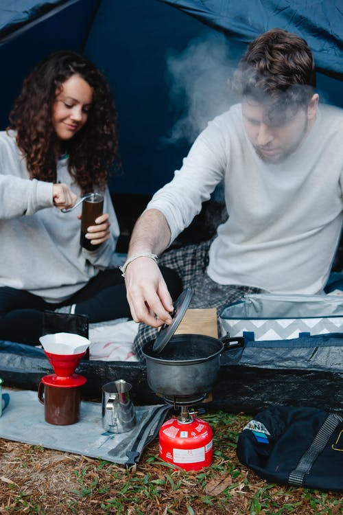 Young glad female hiker grinding coffee near boyfriend behind steam heating water in pot on burner stove in campsite
