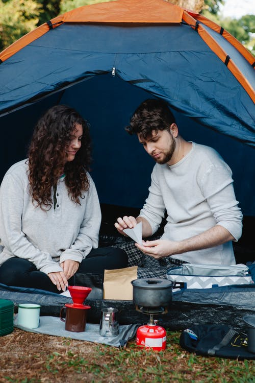 Young bearded male hiker with paper filter near smiling female partner preparing hot drink in campsite
